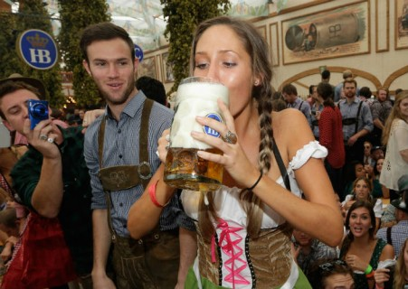 Revellers reach for the first beer mugs at Hofbraeuhaus beer tent during the opening day of the 2014 Oktoberfest on September 20, 2014 in Munich, Germany. The 181st Oktoberfest will be open to the public from September 20 through October 5 and traditionally draws millions of visitors from across the globe to the the world's largest beer festival. (Photo by Johannes Simon/Getty Images)